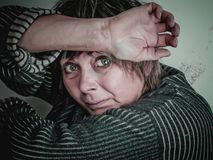 Fearful women with big eyes full scary. Despair and social issue. Fearful woman of middle age hopelessly closed her face with her hands Royalty Free Stock Photos