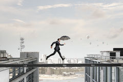 Fearless businessman overcoming difficulty. Mixed media . Mixed media. Businessman with umbrella running on balk above gap. Mixed media Stock Photo