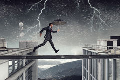 Fearless businessman overcoming difficulty. Mixed media Royalty Free Stock Images