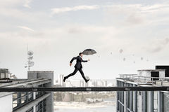 Fearless businessman overcoming difficulty. Mixed media Stock Photos