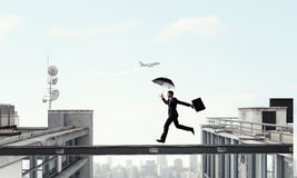 Fearless businessman overcoming difficulty. Mixed media Stock Photography