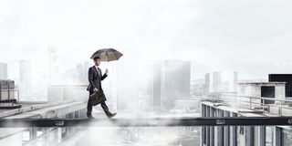 Fearless businessman overcoming difficulty. Mixed media Stock Image