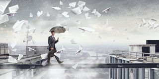 Fearless businessman overcoming difficulty. Mixed media Stock Images