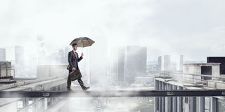 Fearless businessman overcoming difficulty. Mixed media Royalty Free Stock Image