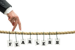 Fearless concept. With the word fearless in alphabet letters hanging on wires from a rope with a businessman walking over the tightrope with his fingers , on Stock Image