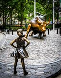 Fearless Girl and Charging Bull. Fearless Girl, which measures approximately 50 inches (130 cm) tall and weighs about 250 pounds (110 kg&#x29 royalty free stock photos