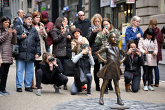 Fearless Girl. People taking pictures of `The Fearless Girl` statue in Lower Manhattan erected to honor International Women`s Day Royalty Free Stock Photography