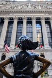 The Fearless Girl statue facing The New York Stock Exchange NYSE building royalty free stock photo