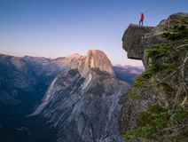 A fearless hiker is standing on an overhanging rock enjoying the view towards famous Half Dome at Glacier Point, Yosemite National. A fearless hiker is standing stock photo