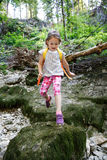 Fearless little girl scout jumping over stones royalty free stock photography