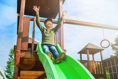 Fearless little girl sliding on playground alone in sunny weather Royalty Free Stock Images