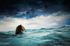 Fearless in Storm. Brave Girl is Facing Big Storm Coming in the Sky while Swimming in the Ocean Stock Photography