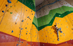Fearless woman climbing up the orange wall in gym Royalty Free Stock Images