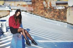 Fearless young girl sitting an iron roof on blurred background of old brick walls. Fearless young girl sitting on an iron roof on a blurred background of old Royalty Free Stock Photography