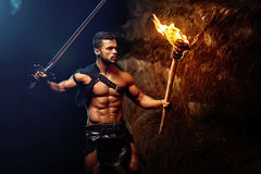 Fearless young muscular warrior with a torch in the dark Royalty Free Stock Photography
