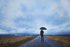Fears and solitude, psychology concept. Psychology concept, man with umbrella standing on the road, fears and solitude Stock Images