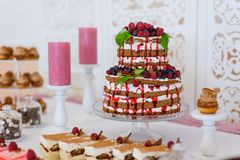 A feast of cakes served on the buffet.sweet desserts with berries and fruit served on the buffet.Fruit Wedding Cake. Holiday cakes and serve.sweet desserts with stock image