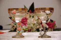 Feast glasses. Bride's and groom's glasses with the   bouquet in background Stock Photos