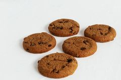 Feast of taste. Sugar ruddy shortbread homemade cookies with raisins and pieces of dark milk chocolate on a light concrete backgro royalty free stock photo