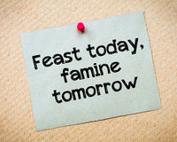 Feast today, famine tomorrow. Message. Recycled paper note pinned on cork board. Concept Image Stock Image