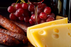 Feast. Wine, cheese, sausage and grapes at a feast Royalty Free Stock Images