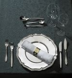 Feastful place setting on green tablecloth Royalty Free Stock Photography