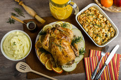 Feasting - stuffed roast chicken with herbs. Mashed potatoes with oregano leaves and homemade stuffing with herbs, freshly squeezed orange juice, fresh fruits Royalty Free Stock Images