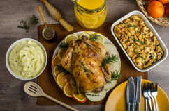 Feasting - stuffed roast chicken with herbs. Mashed potatoes with oregano leaves and homemade stuffing with herbs, freshly squeezed orange juice, fresh fruits Royalty Free Stock Photography