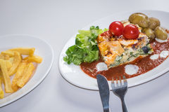 Feat and spinach quiche with chips. Feat and spinach layered quiche served with tomato sauce, cherry tomatoes and roast potatoes Stock Photo