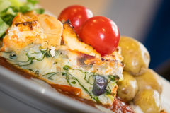 Feat and spinach quiche close up. Feat and spinach layered quiche served with tomato sauce, cherry tomatoes and roast potatoes Royalty Free Stock Image