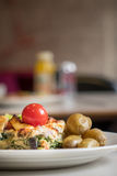 Feat and spinach quiche. Feat and spinach layered quiche served with tomato sauce, cherry tomatoes and roast potatoes Stock Photo