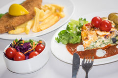 Feat and spinach quiche. Feat and spinach layered quiche served with tomato sauce, cherry tomatoes and roast potatoes and fish and chips meal with side salad Royalty Free Stock Photo