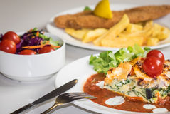 Feat and spinach quiche. Feat and spinach layered quiche served with tomato sauce, cherry tomatoes and roast potatoes and fish and chips meal with side salad Royalty Free Stock Image