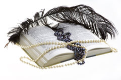 Feather. Open book on white background, beads and feather lying on the book Royalty Free Stock Photography