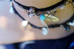 Feather anklet. Close up of travel anklets decorated by shells, beads and a feather charm Royalty Free Stock Images