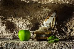 Feather in antique ink bottle and an apple in sandstone cave background. Feather in antique ink bottle and an apple and ivy leaf in sandstone cave background Stock Photos