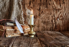 Feather and book novel close to the a candle Royalty Free Stock Photography