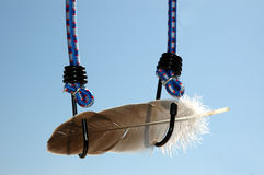 Feather and bungee cord. Two bungee cords holding a feather stock photography