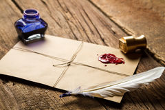 Feather on envelope with red sealant and inkwell Royalty Free Stock Photos