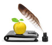 Feather in ink bottle and workbook with an Apple Royalty Free Stock Photo