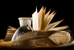 Feather with the inkpot. A feather with the bottle full of ink and a book Stock Photo