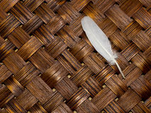 Feather isolated on wood weave background Royalty Free Stock Image
