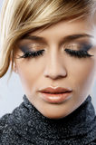 Feather Makeup. Beautiful blond woman with artistic feather makeup Stock Image