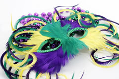 Feather mardi gras mask with beads. Feathered Mardi Gras mask laying on colorful beads Royalty Free Stock Photos