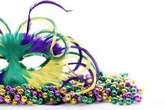 Feather mardi gras mask on beads. Feathered Mardi Gras mask laying on colorful beads Stock Photos