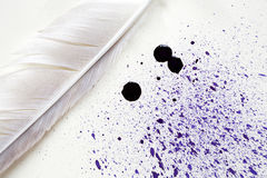 Feather Near Ink Blobs. Art concept. Closeup of quill near blue ink blobs on paper background Royalty Free Stock Photos