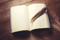 Feather on a notebook. A feather on a notebook, blank pages for writing and drawing royalty free stock photo