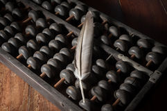Feather on old abacus. Stock Images