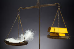 The feather outweighs a stacks of golden bars. Stock Images