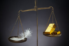 The feather outweighs a stacks of golden bars. Stock Photo